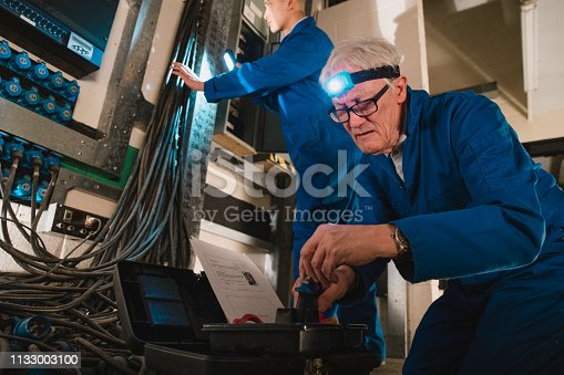 istock Electricians Fixing a Switch Board 1133003100