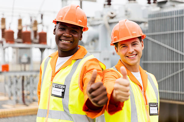 electricians giving thumb up in substation stock photo