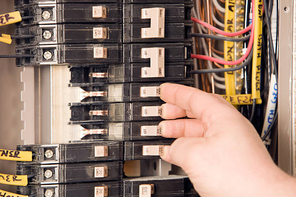 electrician's hand turning on circuit breakers - fuse box stock photos and pictures