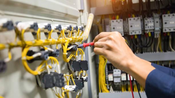 elektriciens handen huidige elektrische testen in het configuratiescherm. - elektrische fitting stockfoto's en -beelden