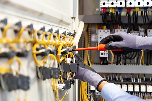 Electricians work to connect electric wires in the system.