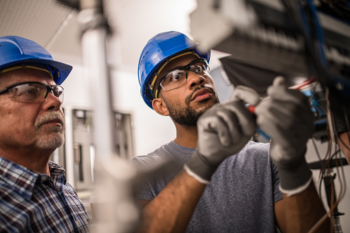 Photo of a senior caucasian and young African-American electrician working on a fuse box.