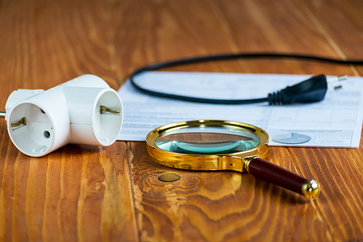 istock Electricity Bill on a table with magnifier and Electric Splitter 939514554