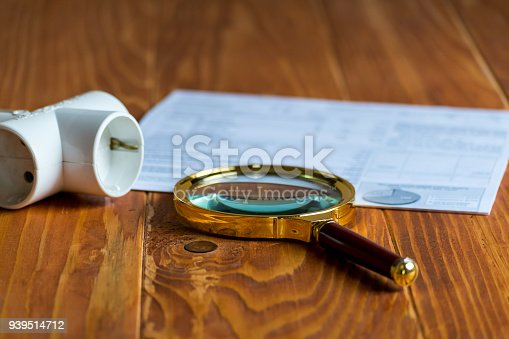 istock Electricity Bill on a table with magnifier and Electric Splitter 939514712