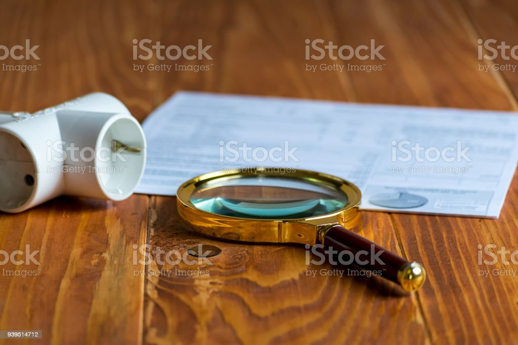 Electricity Bill on a table with magnifier and Electric Splitter stock photo