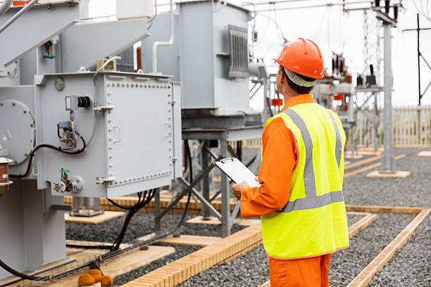 electricity company substation worker - transformers stock photos and pictures