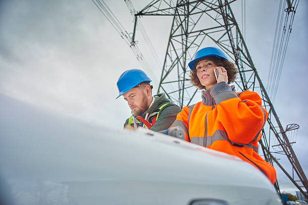 electricity engineers beneath a pylon male and female engineers beneath an electricity pylon looking at plans on the bonnet of their van . The female engineer is on the phone. electricity pylon stock pictures, royalty-free photos & images