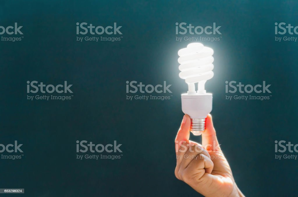 electricity, environment and ecology concept - close up of hand holding energy saving lightbulb stock photo