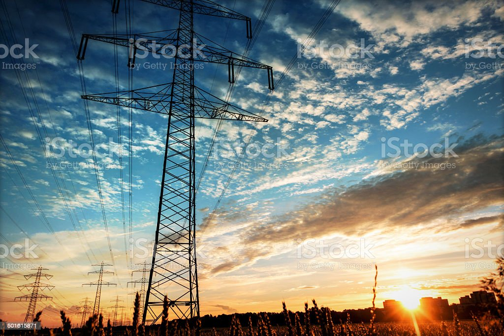 Electricity industry high voltage towers at sunset stock photo