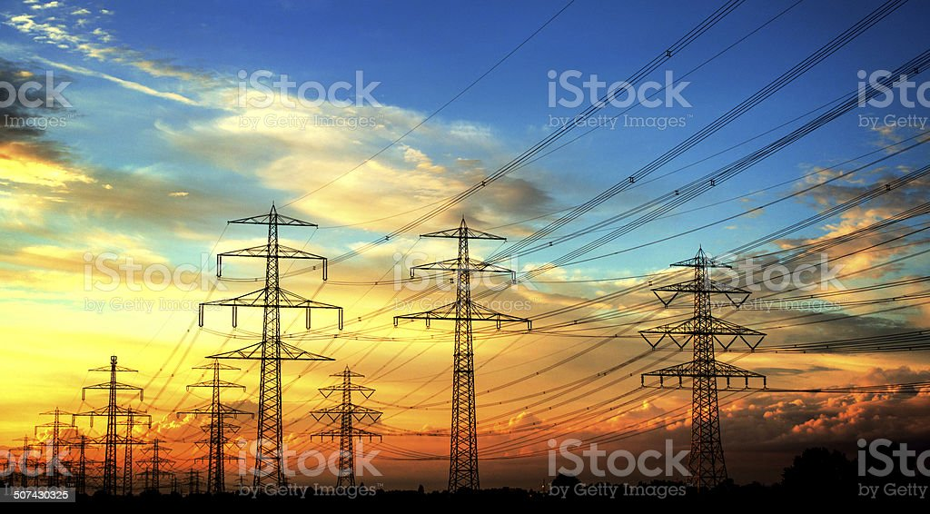 Electricity industry - high voltage towers in a row stock photo
