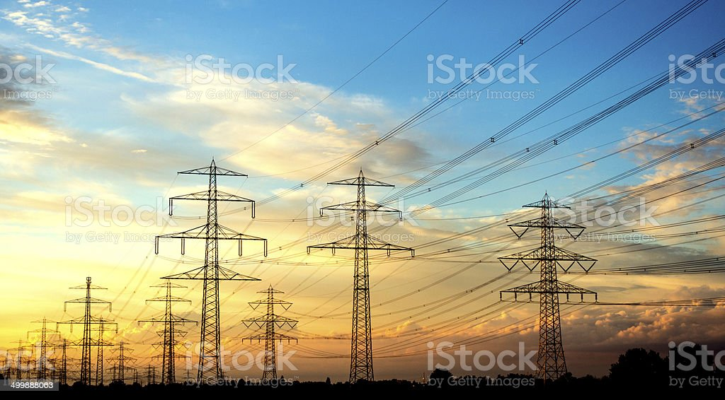 Electricity industry - many high voltage towers at sun set stock photo