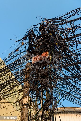 Electricity pole with dozens of dangerous untidy messy cables and wires