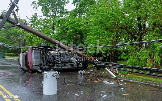 istock Electricity poles fall because of storms. damaged car 960097884
