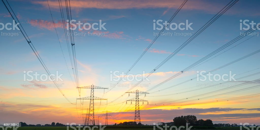Electricity poles in an empty landscape during sunset stock photo