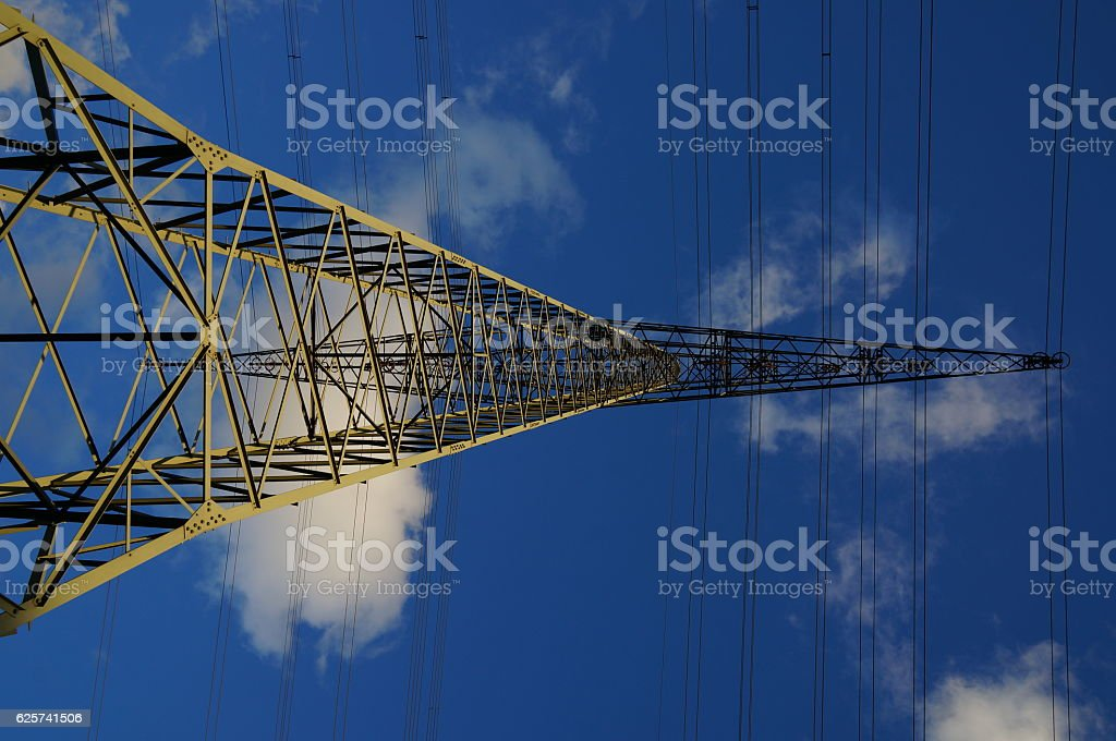 electricity pylon against blue sky with white clouds stock photo