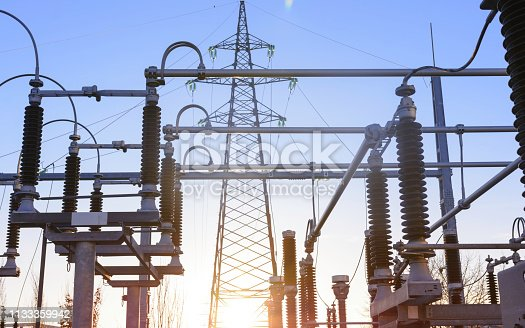 Power station on a sunset, close up of a high voltage transformer in power substation.