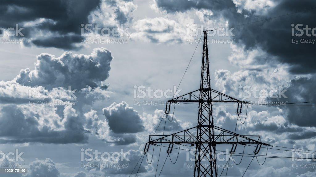 Electricity pylon top on a cloudy sky background stock photo