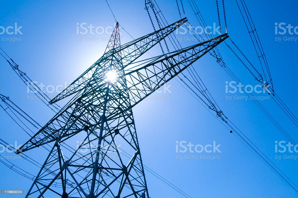 Electricity pylon with blue sky and sun royalty-free stock photo