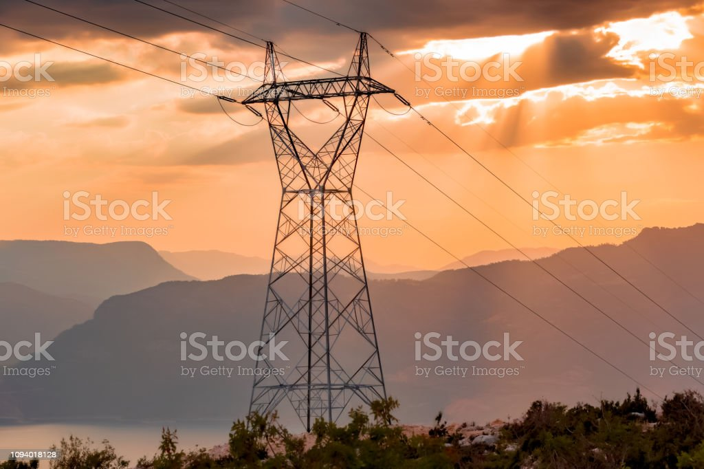 Electricity Pylon with Mountains, Back lit, Dam Lake and Sunset