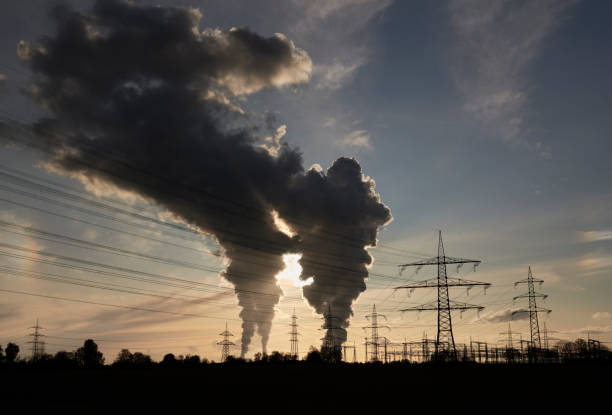 Electricity pylons and two coal fired power plants with pollution stock photo