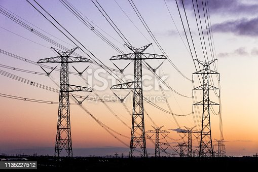 Electricity pylons during dusk evening sky sunset.