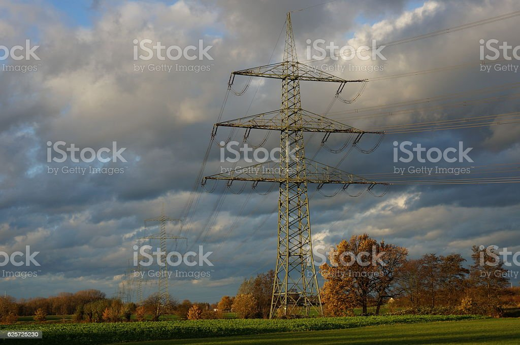 electricity pylons in a row in green landscape stock photo