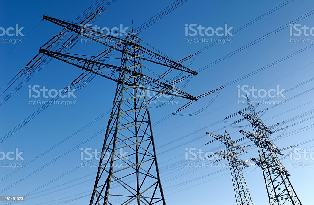 Electricity pylons standing tall under the clear, blue sky royalty-free stock photo