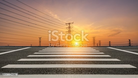 Electricity tower silhouette and empty asphalt road at dusk