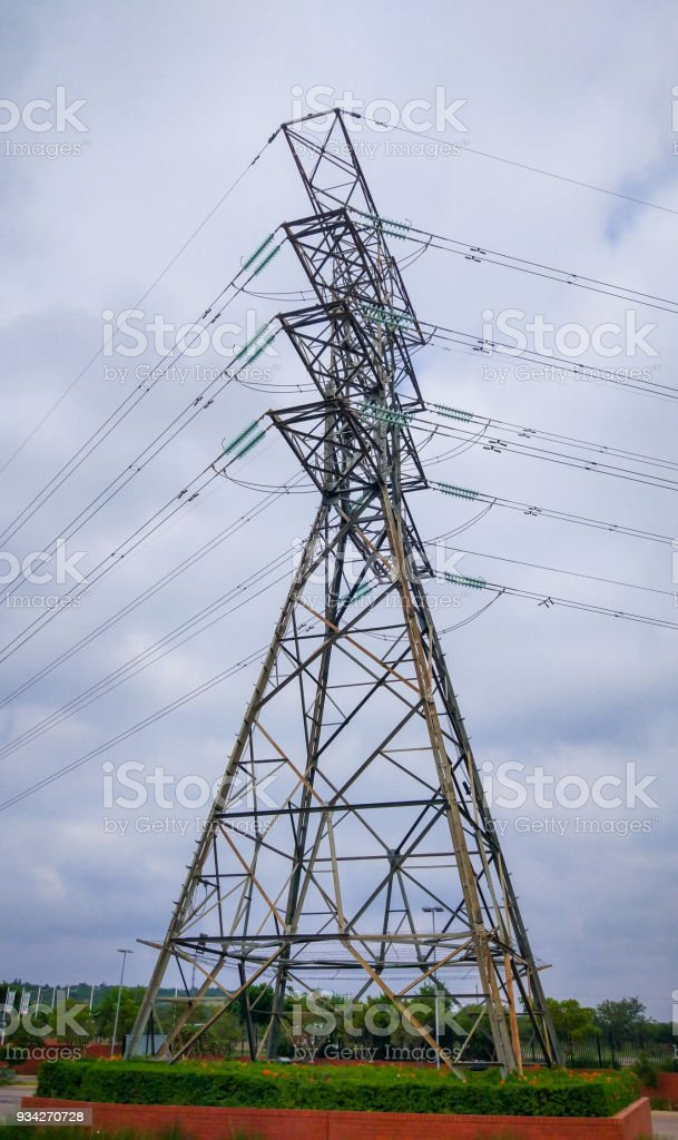 Electricity transmission mast with cloudy background and green base