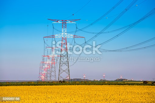600401714istockphoto Electricity transmission pylon silhouetted against blue 539989186