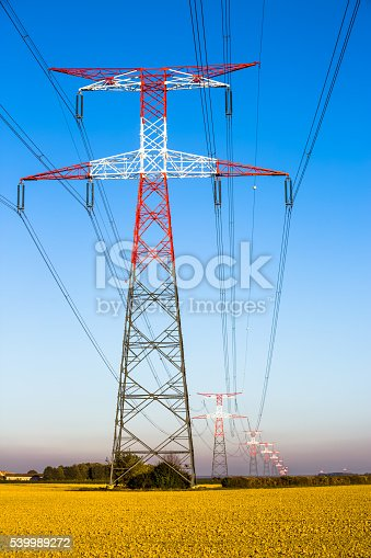 600401714istockphoto Electricity transmission pylon silhouetted against blue 539989272