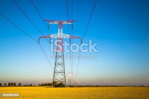 600401714istockphoto Electricity transmission pylon silhouetted against blue 539989366