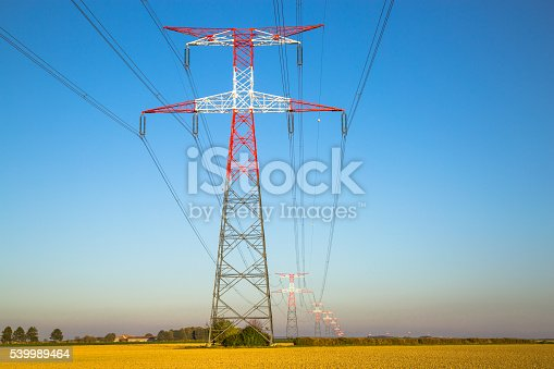 600401714istockphoto Electricity transmission pylon silhouetted against blue 539989464