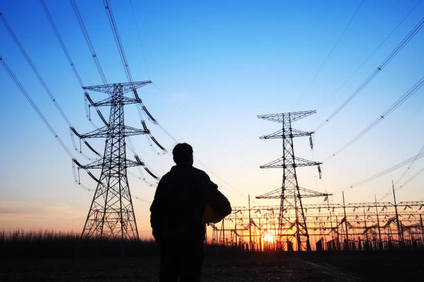 Electricity workers and pylon silhouette stock photo