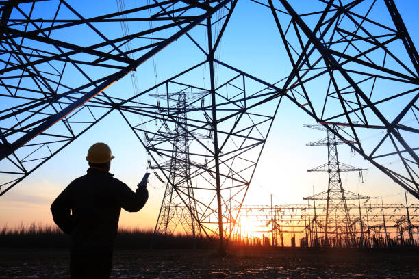 pracownicy elektryczni i sylwetka pylonu - przewód składnik elektryczny zdjęcia i obrazy z banku zdjęć