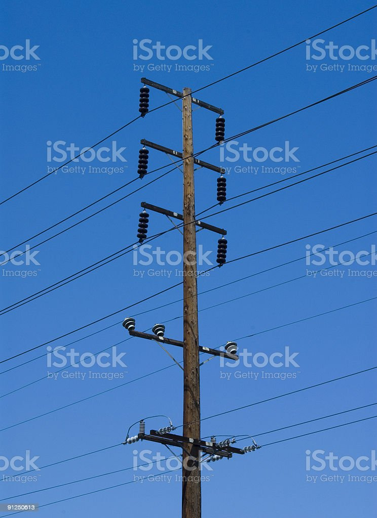 Electricty lines on power poles with blue sky background royalty-free stock photo
