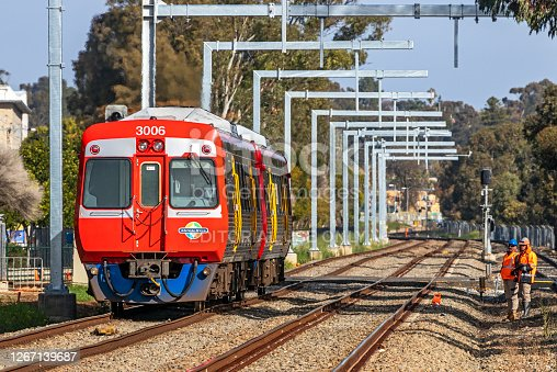 Adelaide, Australia - August 19, 2020: Two surveyors from the Gawler Line Electrification works stand clear as an Adelaide Metro diesel commuter train passes by under newly-erected overhead wire stanchions.