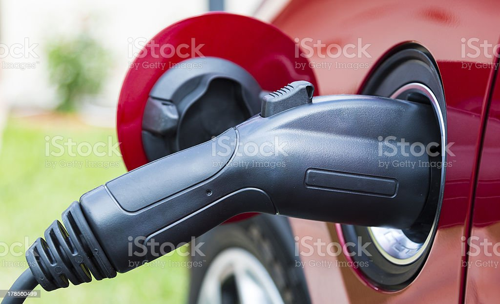 Electriv vehicle plugged in royalty-free stock photo