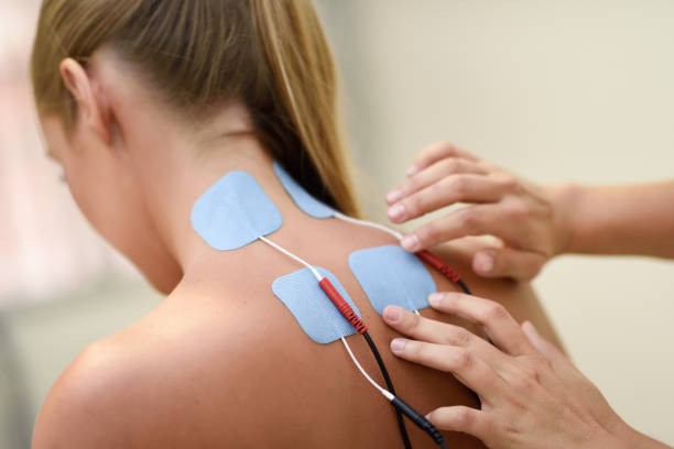 Electro stimulation in physical therapy to a young woman stock photo