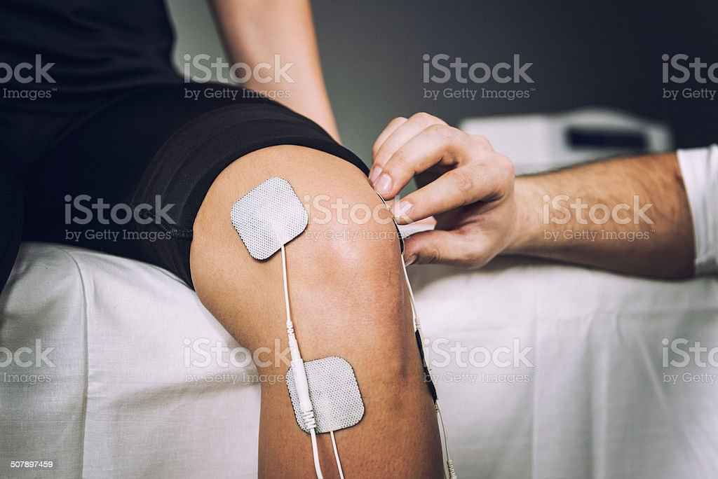 Electro stimulation used to treat knee pain stock photo