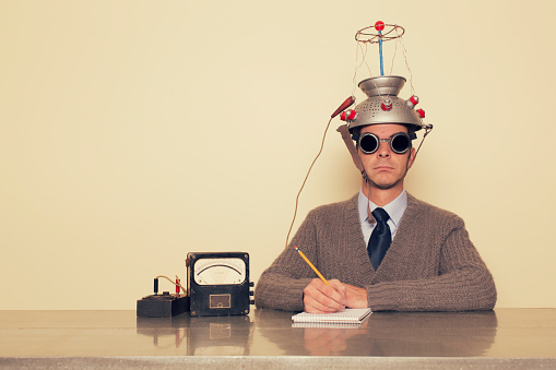 A man is testing the limits of the mind by placing a mind reading invention on his head trying to understand the brain. He is dressed in retro sweater and tie with safety goggles waiting to measure brain waves and understand the unknown.