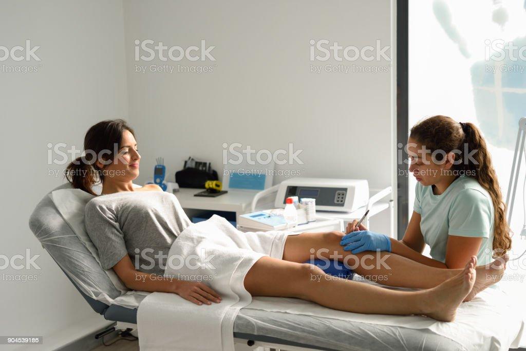 Electroacupuntura en seco con la aguja en la rodilla femenina - foto de stock