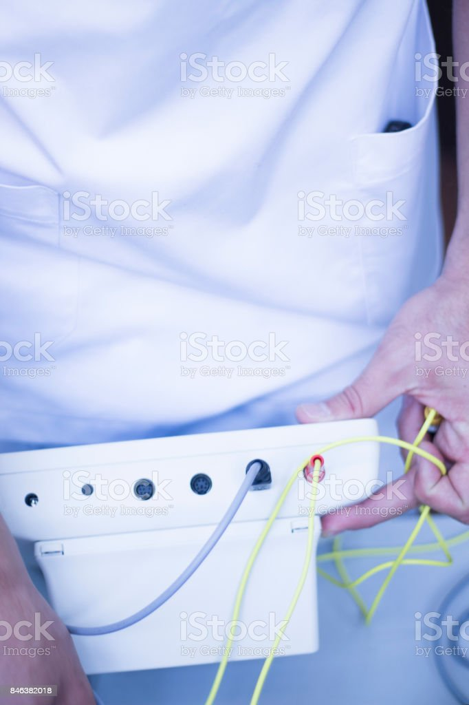 Electroacupunture cables connecting machine used by acupunturist on patient in pain and injury acupunture with electrical pulse treatment stock photo