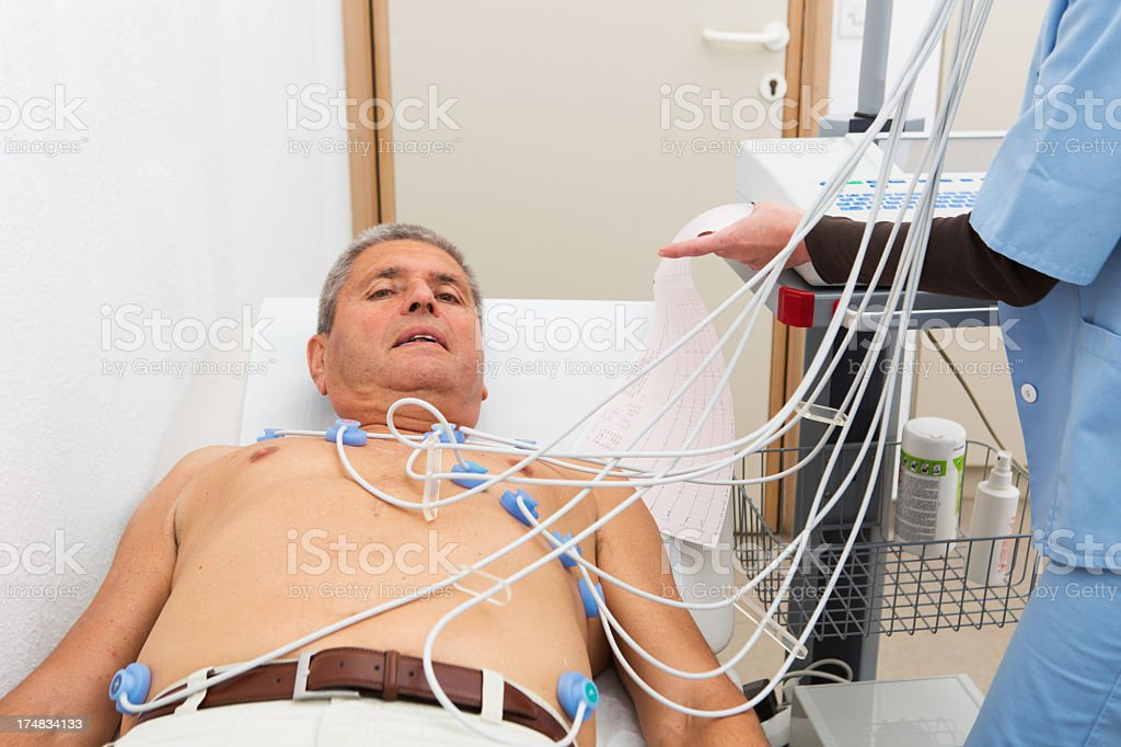 Electrocardiography...senior at the doctor,checking ECG royalty-free stock photo