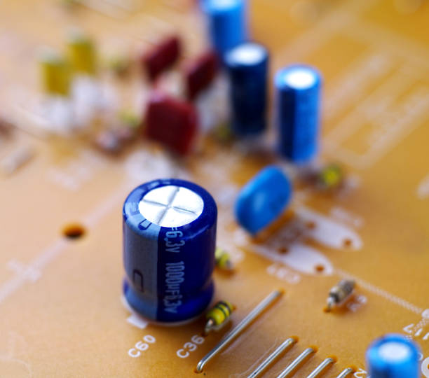 electrolytic capacitor on printed circuit board, macro, selective focus - capacitor stock photos and pictures