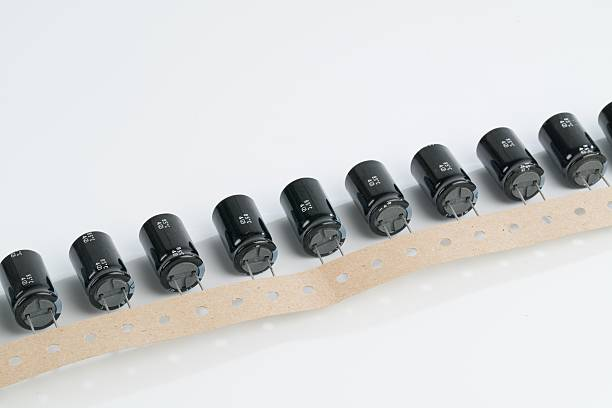 electrolytic capacitors on a white background - capacitor stock photos and pictures