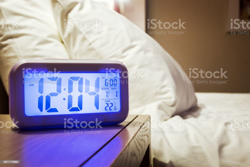 electronic alarm clock stands on a bedside table in the room stock photo