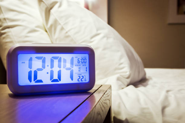 Elektronischer Wecker steht auf einem Nachttisch im Zimmer – Foto