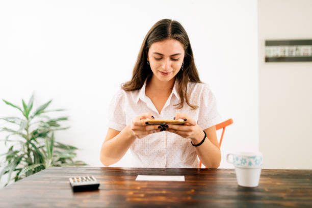 Electronic Banking from cell phone Latin woman takin photo of a check with cell phone bank deposit slip stock pictures, royalty-free photos & images