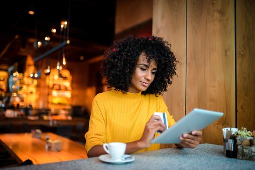 Beautiful smiling African American woman using digital tablet at the bar.